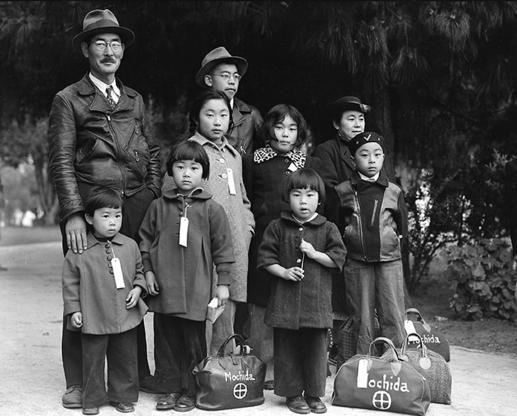Hayward, California, May 8,1942. Members of the Mochida family awaiting evacuation bus. Photographer: Dorothea Lange